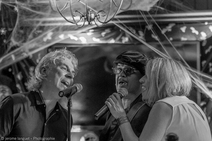Deux chanteurs et une chanteuse en train de chanter ensemble derrière un micro lors d'un événement signé Misterlive Prod