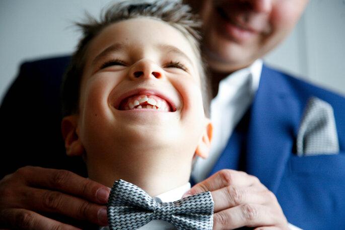 Niño sonriendo mientras su padre le organiza el corbatín