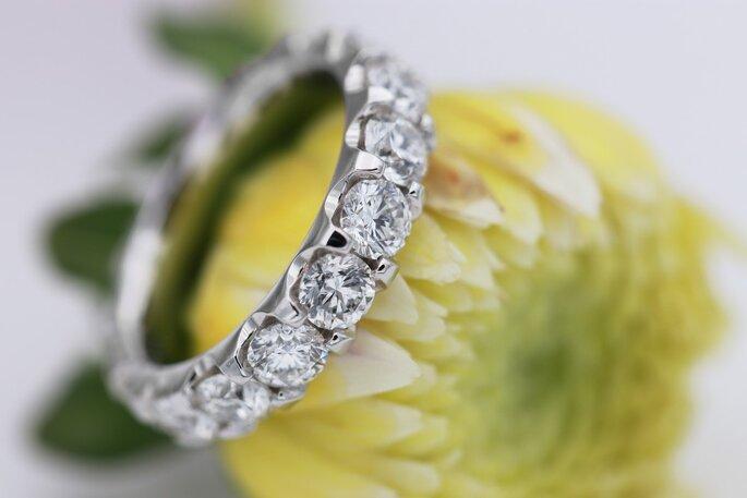 La Maison de l'Alliance & du Diamant - Une alliance sertie de diamants, en argent, disposé sur une pivoine jaune