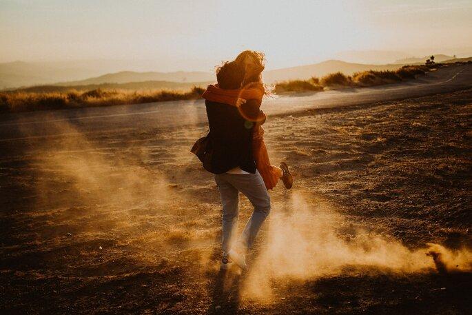 rapaz com rapariga ao colo em cenário desértico poeira casal