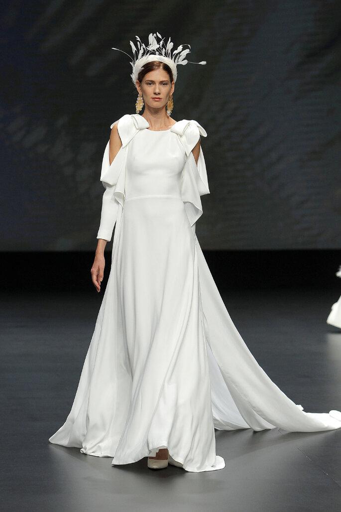 Colección Vestido de Novias 2021 Jesús Peiró vestido de novia entallado con larga capa, cola y magas asimétricas largas decoradas con volantes