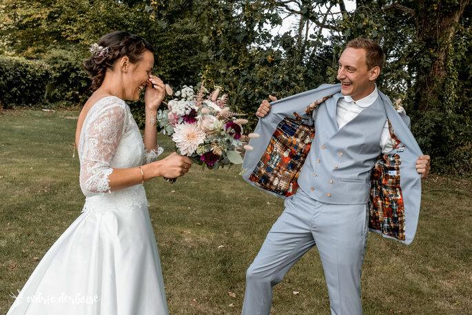 Un couple de marié s'amusant dans les jardins de leur lieu de réception, pendant la séance photos.