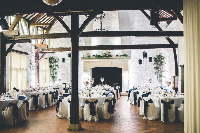 Une salle de réception rustique pour un mariage avec de hauts plafonds et des poutres apparentes