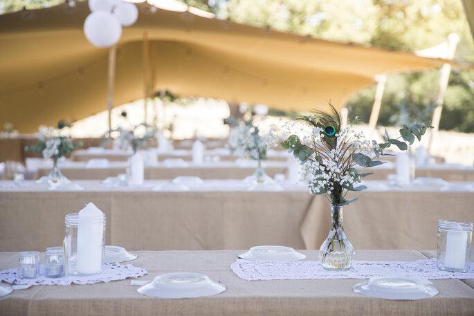 Tables installées pour un dîner de réception sous tente.