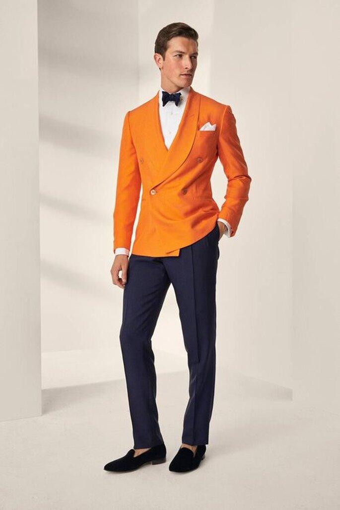 smoquin alternativo en color naranja con moño negro y pantalon azul traje de novio para la boda