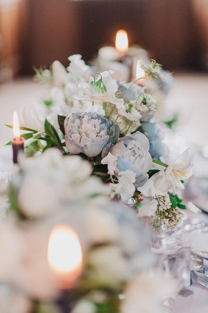 Une composition florale dans des tons bleus et blancs accompagnée de bougies orne une réception de mariage