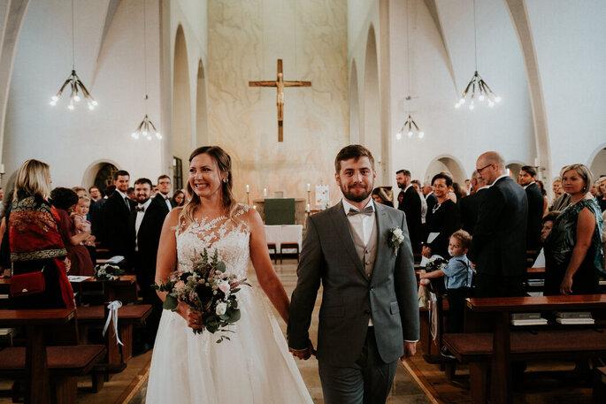 Ein Brautpaar schreitet nach dem Ja-Wort den Kirchengang entlang.