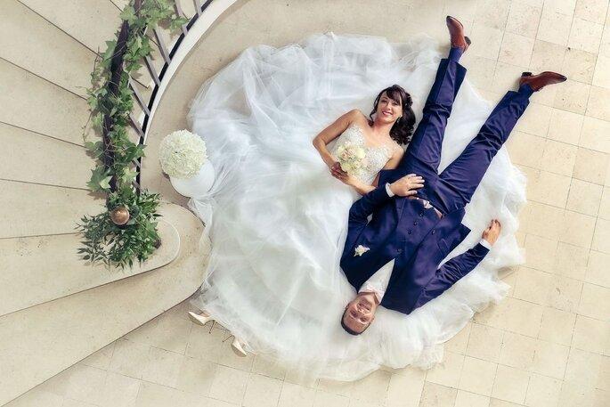Deux mariés couchés en bas d'un escalier font une photo originale le jour de leur mariage
