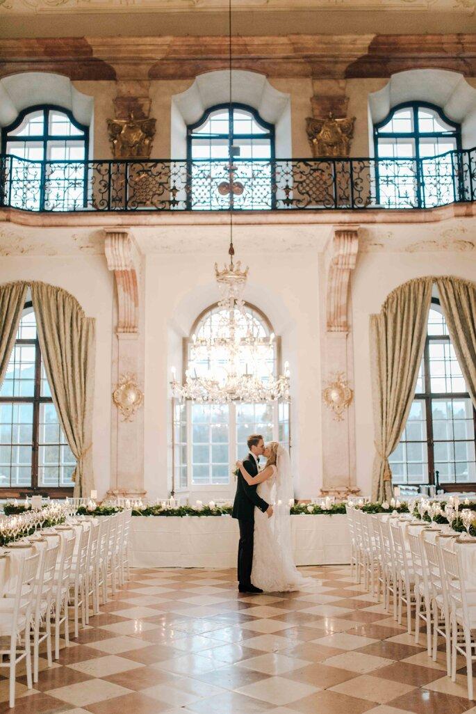 sich umarmendes Brautpaar im Saal Schloss