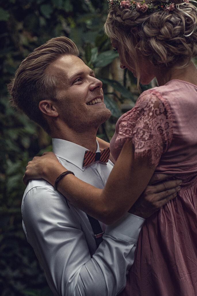 Verliebt hält der Bräutigam die Braut in seinen Armen und schaut ihr in die Augen. Im Hintergrund ist ein Garten zu sehen.