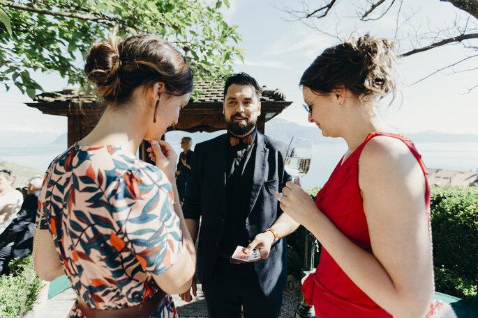 Le magicien en train de réaliser un tour de cartes à deux invitées pendant le vin d'honneur
