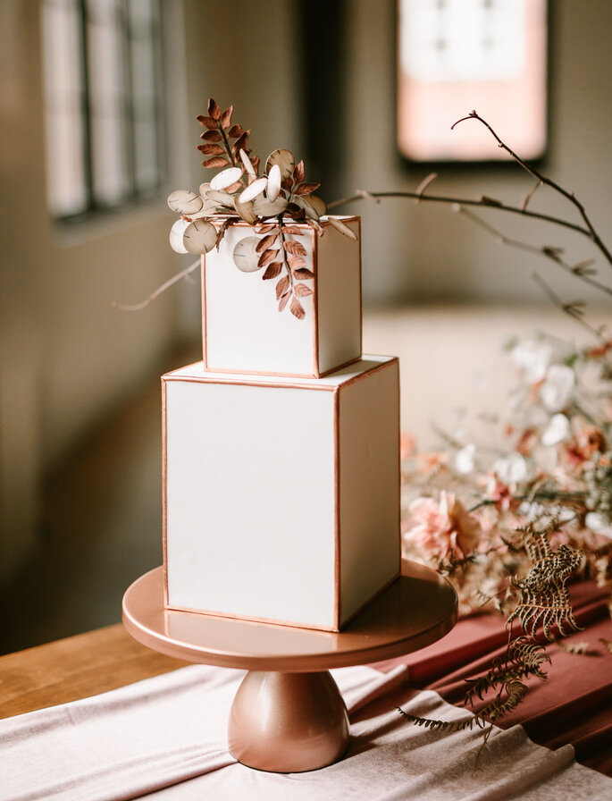 Torta para matrimonio en forma geométrica decorada con ramas y flores