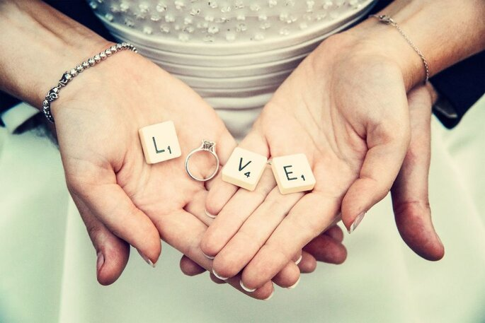 """Des lettres de Scrabble formant le mot """"LOVE"""" dans les mains d'une mariée"""