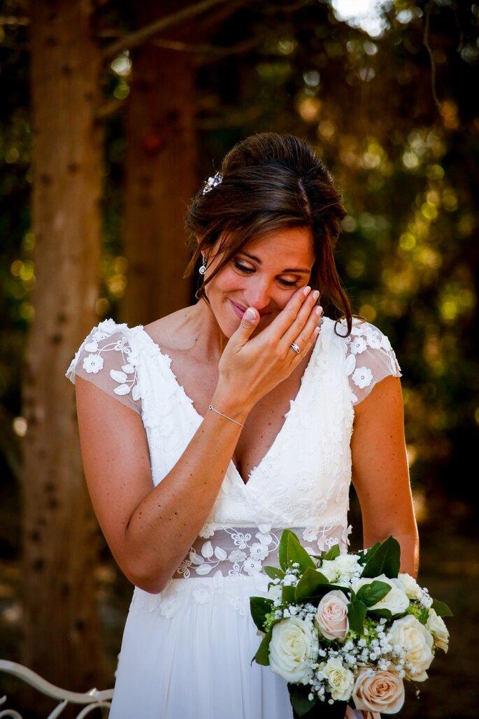 Une mariée émue, un bouquet de roses blanche à la main, qui essuie ses larmes de joie