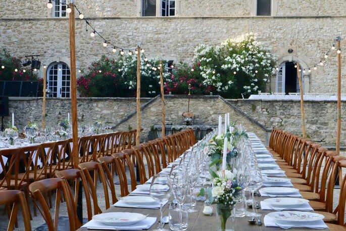 Un banquet de mariage aux airs de guinguette : grandes tables, mobilier rustique, belle vaisselle et lampions