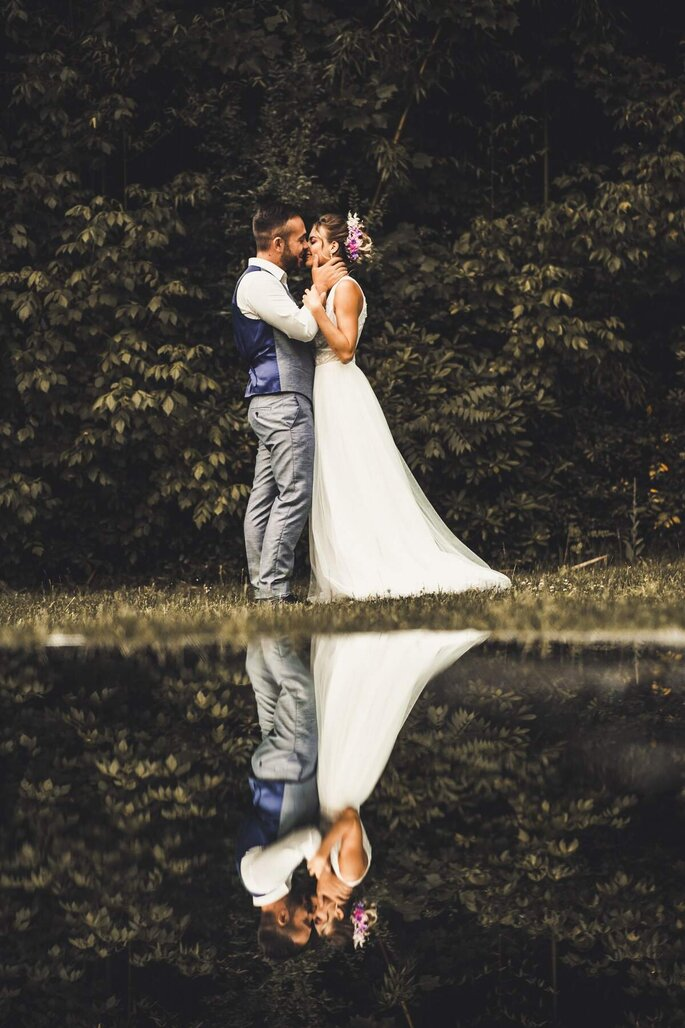 Séance photo d'un couple de mariés. On voit son reflet dans l'eau.