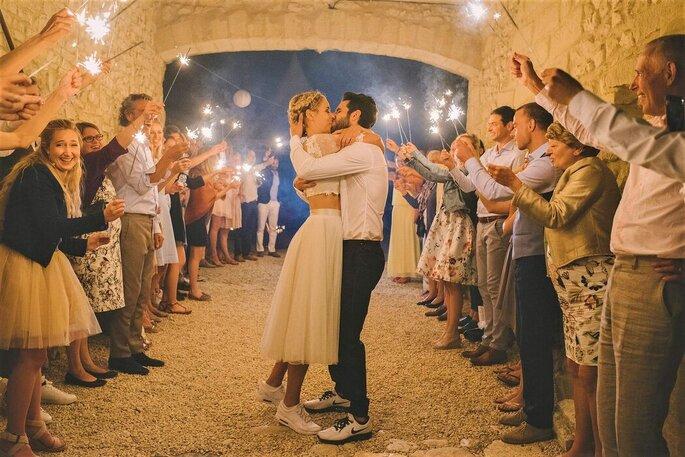 Deux mariés s'embrassent, entourés de leurs invités qui leur font une haie d'honneur