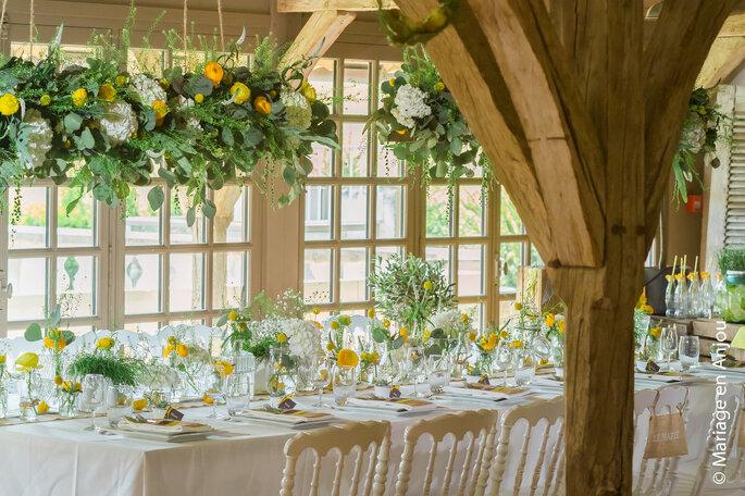 Table de réception décorée avec des bouquets de fleurs. D'autres sont suspendus au-dessus de la table.