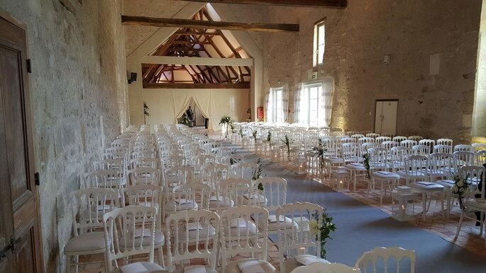 Chaises blanches disposées pour une cérémonie laïque en intérieur dans une salle de réception du Château de Serans