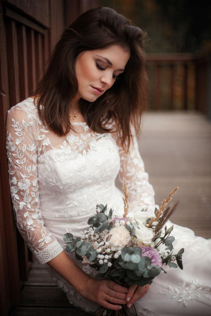 Eine Braut sitzt nachdenklich auf einem Holzboden und schaut ihren Brautstrauß an.