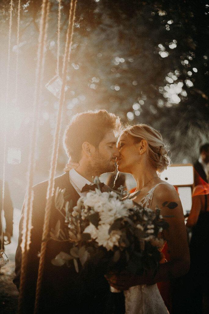 Les mariés s'embrassent au milieu de leur réception de mariage