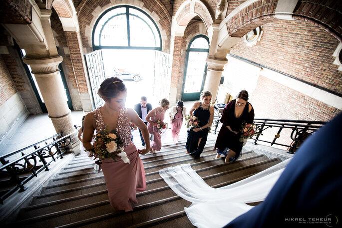 Les demoiselles d'honneur suivent les mariés qui montent les marches de la mairie