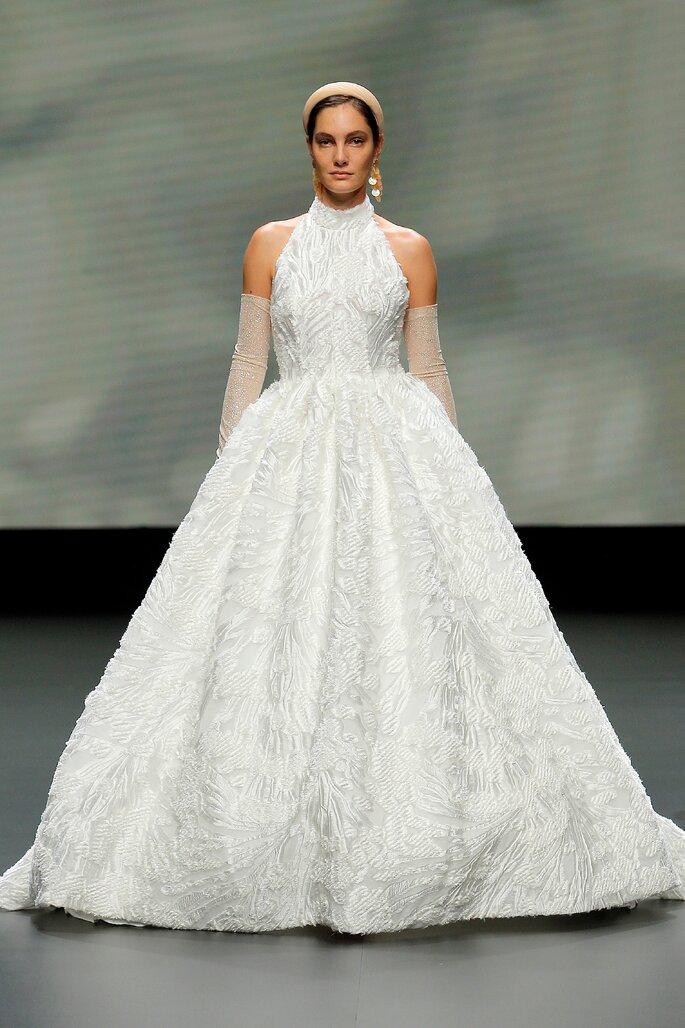 Colección Vestido de Novias 2021 Jesús Peiró vestido de novia en corte princesa con cuello alto, decorado con bordados y complementado con guantes transparentes