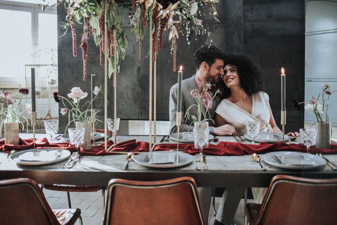Das Brautpaar sitzt am dekorierten Hochzeitstisch und hält sich in den Armen, organisiert von Freakin' Fine Weddings.