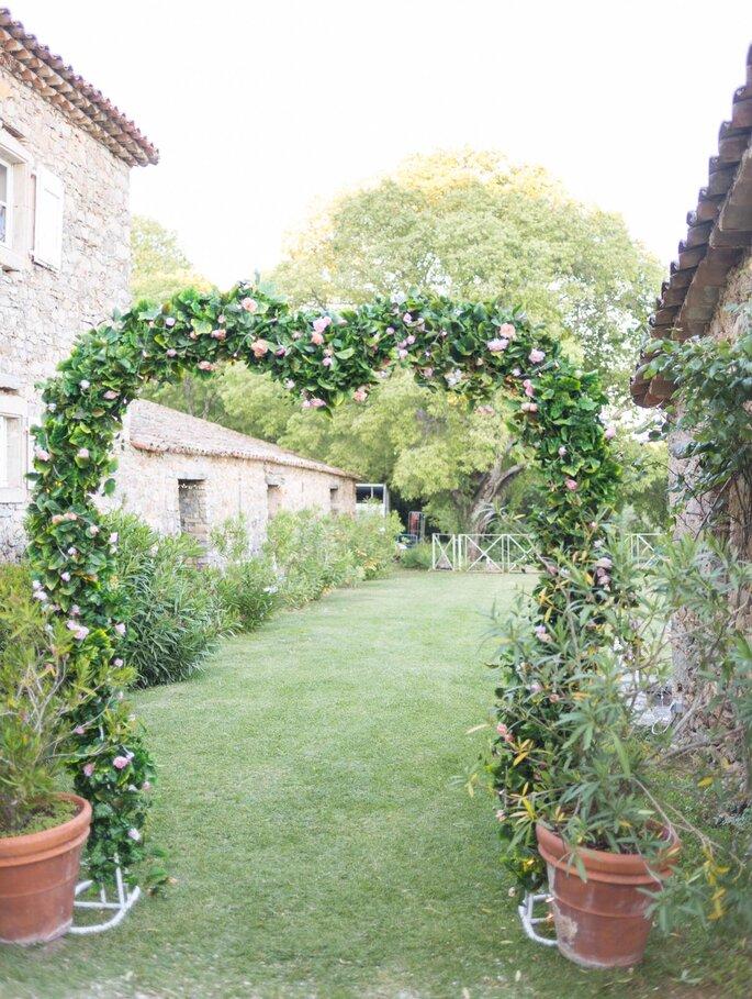 Arche de roses et de lierres qui ouvre un chemin entre deux bâtiments aux murs en pierres apparentes