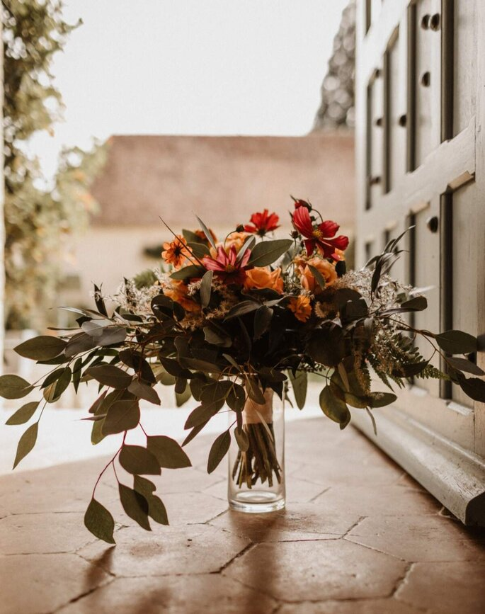 Le bouquet de la mariée fait de végétaux et de fleurs ocres a été posé dans un vase.