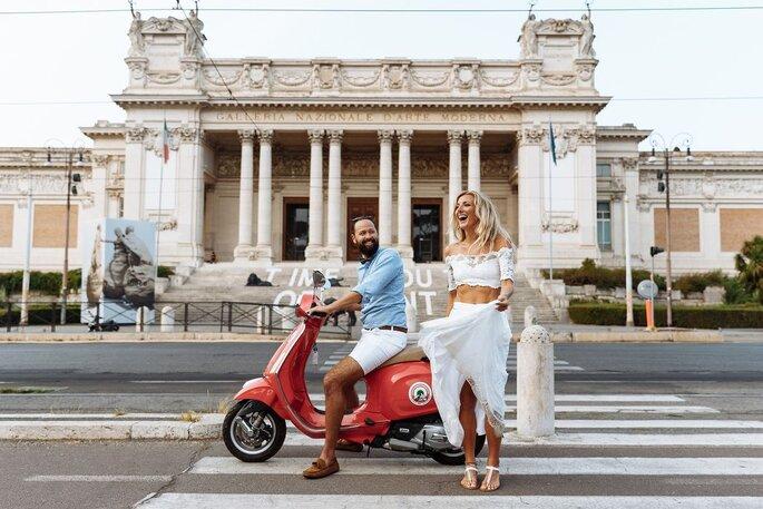 Deux mariés en train de profiter d'un tour en scooter en italie