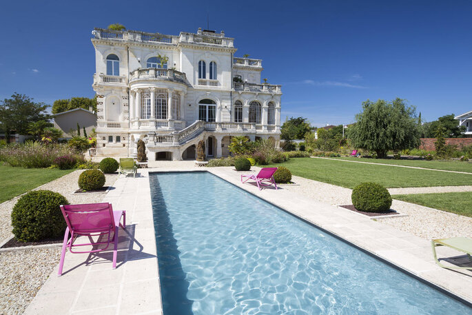 Beau château de style Belle Epoque avec sa longue piscine dans un parc paysager parfaitement entretenu