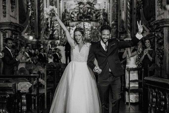 Noivos saindo da igreja após casamento