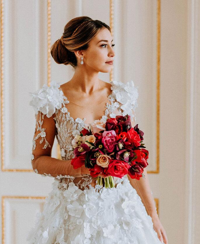 noiva com cabelo apanhado e um bouquet em tons vermelhos vestido rendando com mangas transparentes