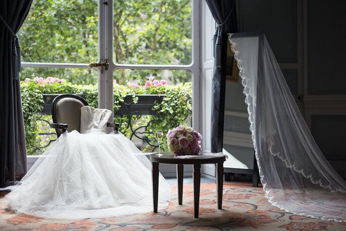 Une robe de mariée posée sur un fauteuil face à la fenêtre.