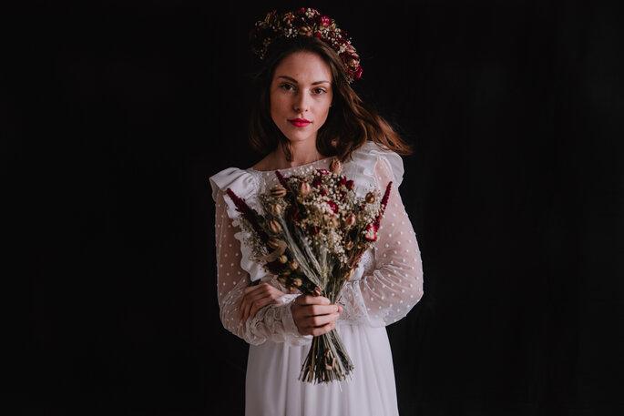Une mariée tenant un bouquet de fleurs séchées à la main.