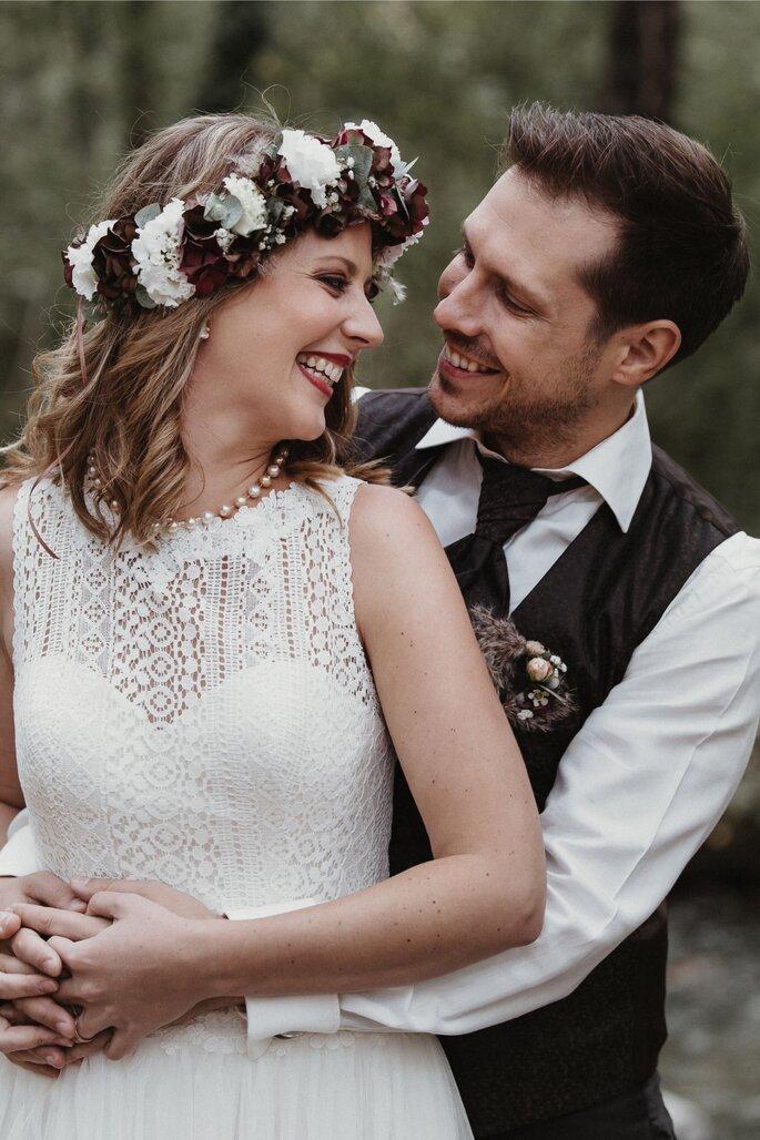 Das Brautpaar lächelt sich an.
