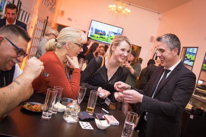 Un tour de magie avec jeu de cartes est réalisé à une table d'invités.