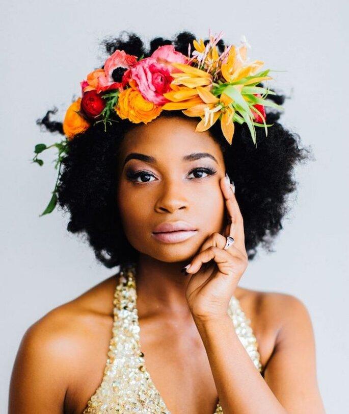 Une mariée afro - métisse portant une coiffure pour cheveux courts avec une grosse couronne de fleurs exotiques pour son mariage