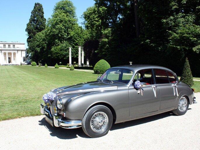 Jaguar gris métallisé rétro garée devant un château décorée pour un mariage