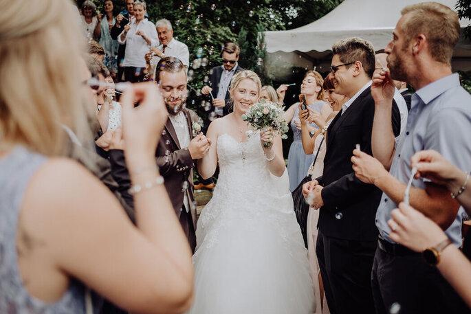 Ein Brautpaar läuft nach dem Ja-Wort durch die Reihen der Hochzeitsgesellschaft.
