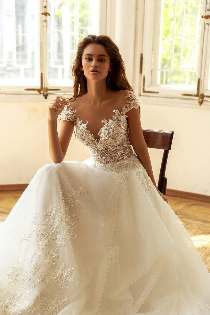 Robe de mariée au bustier fait de jeu de dentelle transparente et orné de perle, jupe en tulle brodée