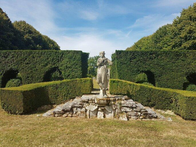 Une statue au milieu du parc et des jardins propices à un mariage