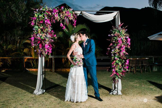 Noivos se beijam em decoração com flores