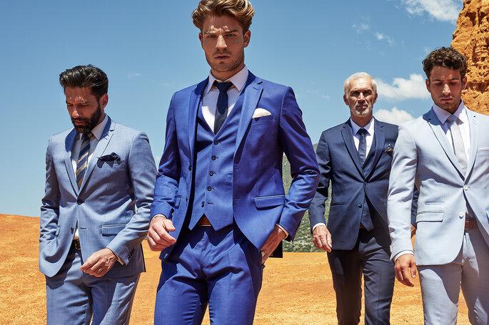 Quatre hommes marchant dans le désert avec des costumes bleus différents de la marque Father & Sons