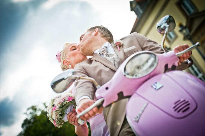 Ein Brautpaar fährt auf einer pinken Vespa und küsst sich dabei.
