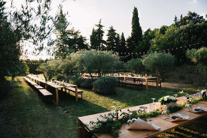 Mariage champêtre organisé en plein air avec des tables en bois et guirlandes guinguettes