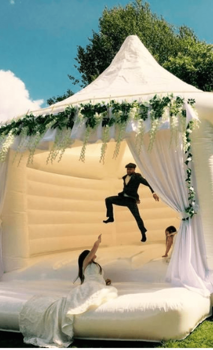 Brautpaar hüpft in einer weiß verzierten Hüpfburg