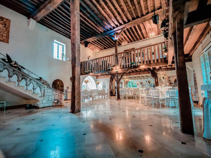 Une salle de réception aux volumes grandioses et au cachet ancien grâce à ses poutres apparentes et piliers en bois massif