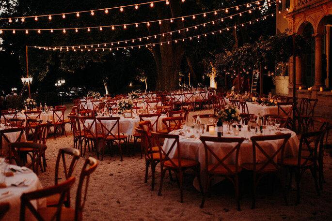 Dîner de mariage en extérieur à la tombée de la nuit, à la lueur des lampions